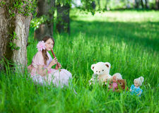 Girl in pink dress playing the flute favorite toys. Nine-year girl in a pink dress sits in summer garden and playing the flute favorite toys Royalty Free Stock Photos