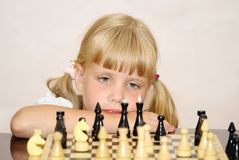The girl in a pink dress plays a chess Royalty Free Stock Photography