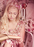 Girl in pink dress reading book Stock Images