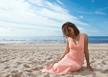 Girl in pink dress on seacoast Stock Photos