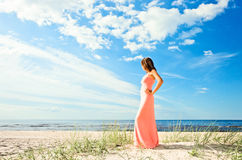 Girl in pink dress on seacoast Royalty Free Stock Photography