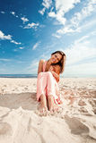 Girl in pink dress on seacoast Stock Images