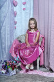 Girl in a pink dress. Sits Stock Photography