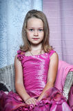 Girl in a pink dress. Sits Royalty Free Stock Images