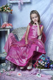 Girl in a pink dress. Sits Stock Photo