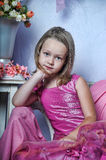 Girl in a pink dress. Sits Stock Images