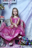 Girl in a pink dress. Sits Royalty Free Stock Photo