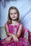 Girl in a pink dress. Sits Royalty Free Stock Photos