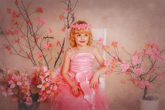 Girl in a pink dress sitting on a chair. Wreath on the head and around the flowers Stock Photography