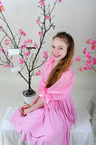 Girl in a pink dress. Sitting near blossoming tree with bird and empty cell Royalty Free Stock Photography