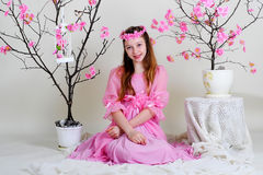 Girl in a pink dress. Sitting near blossoming tree with bird and empty cell Royalty Free Stock Photos
