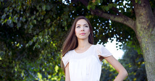 The girl in a pink dress, stands in the park and looks into the distance, beautiful, delicate, female, fashion style Royalty Free Stock Images