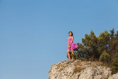 A girl in a pink dress stands on a rock in front of a precipice royalty free stock images