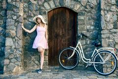 Girl in a pink dress and a straw hat is standing beside a textured stone, old wall with a wooden door stock photos