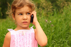 Girl in pink dress talking on cell phone Royalty Free Stock Image
