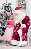 Girl in a pink dress talks to Saint Nicolas Royalty Free Stock Photography
