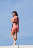 Girl in pink dress walking against the sky Royalty Free Stock Images