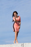 Girl in pink dress walking against the sky Royalty Free Stock Photography