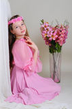 Girl in a pink dress and wreath. Dreamily sits near a vase of flowers Stock Images