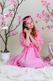 Girl in a pink dress and wreath. Dreamily sits near a vase of flowers Royalty Free Stock Image