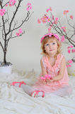 The girl in a pink dress and a wreath on his head. Girl in a pink dress near blooming derevv sitting on the floor and holding flowers Royalty Free Stock Image