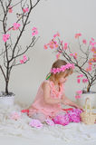 The girl in a pink dress and a wreath on his head. Girl in a pink dress near blooming derevv sitting on the floor and picking flowers Stock Image