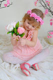 The girl in a pink dress and a wreath on his head. Girl in a pink dress near blooming derevv sitting on the floor and picking flowers Stock Photos
