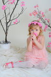 The girl in a pink dress and a wreath on his head. Girl in a pink dress near blooming derevv sitting on the floor and sniffs flowers Royalty Free Stock Photos