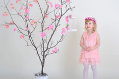 The girl in a pink dress and a wreath on his head. Girl in a pink dress near a flowering tree with a bird that flew out of the cell Stock Image