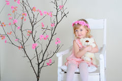 The girl in a pink dress and a wreath on his head. Girl in a pink dress near a flowering tree sits on a chair and holding a stuffed toy bear Royalty Free Stock Photography
