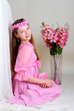 Girl in a pink dress and wreath. Girl in a pink dress sits near a vase of flowers Stock Photography
