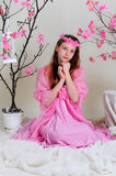Girl in a pink dress and wreath. Girl in a pink dress sits pensively near blossoming cherry tree Royalty Free Stock Image
