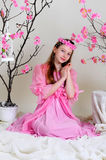 Girl in a pink dress and wreath. Girl in a pink dress sits pensively near blossoming cherry tree Stock Photos