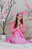Girl in a pink dress and wreath. Girl in a pink dress sits pensively near blossoming cherry tree Stock Image