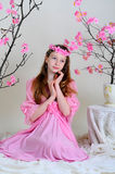 Girl in a pink dress and wreath. Girl in a pink dress sitting near blossoming cherry tree Royalty Free Stock Images
