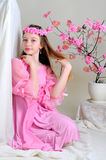 Girl in a pink dress and wreath. Girl in a pink dress sitting near blossoming cherry tree and stroked her hair Stock Photos