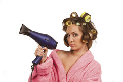 Girl in pink dressing gown with blue hairdryer Stock Photography