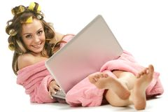 Girl in pink dressing gown sitting with laptop Stock Photo