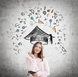 Girl in pink and education icons. Portrait of a girl in a pink cardigan standing near a concrete wall with education icons and graduation hat Royalty Free Stock Photos