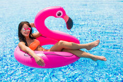 Beauty woman on a pink flamingo in the pool in sunglasses royalty free stock photo