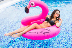 Girl on a pink flamingo in the pool In sunglasses. Summer vocation. Girl on a pink flamingo in the pool In sunglasses Stock Images