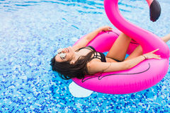 Girl on a pink flamingo in the pool In sunglasses. Summer vocation. Girl on a pink flamingo in the pool In sunglasses Stock Photography