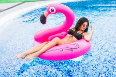 Girl on a pink flamingo in the pool In sunglasses. Summer vocation. Girl on a pink flamingo in the pool In sunglasses Royalty Free Stock Photos