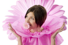 Girl and pink flower. Nice and funny shot of a young and cute girl in pink with flower in mouth looking away Royalty Free Stock Image