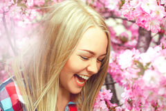 Girl in pink flowers bloom laughs Royalty Free Stock Photography