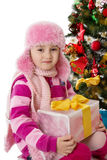 Girl in pink fur hat holding present under Chritmas tree Stock Photo