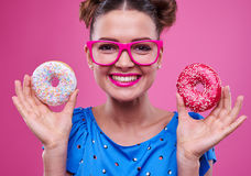 Girl in pink glasses holds a tasty doughnuts and smiling broadly Stock Photography