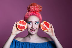 Girl with pink hair with Grapefruit halves on lilac background, place for text Royalty Free Stock Image