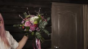 A girl with pink hair holds a variety of flowers in her hands in front of her. The bouquet is decorated with dangling. Silk ribbons. Side view stock video footage