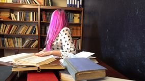 The girl with the pink hair in the library reading books stock video